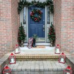 Christmas front porch decor. Red and green decorations. Red lanterns. #Christmasfrontporch #Christmasdecor #holidaydecor